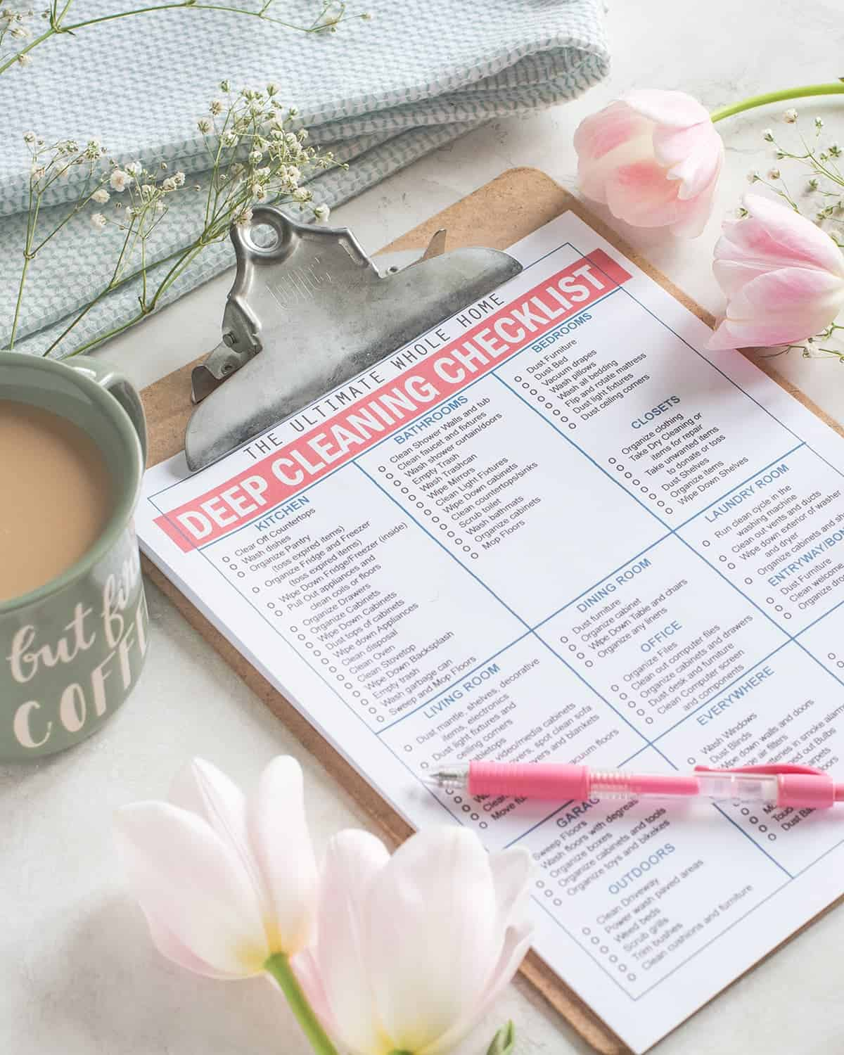Whole Home Cleaning Printable Checklist on clipboard with pink pen. Norwex cloth, baby's breath, pink tulip and coffee cup in background.
