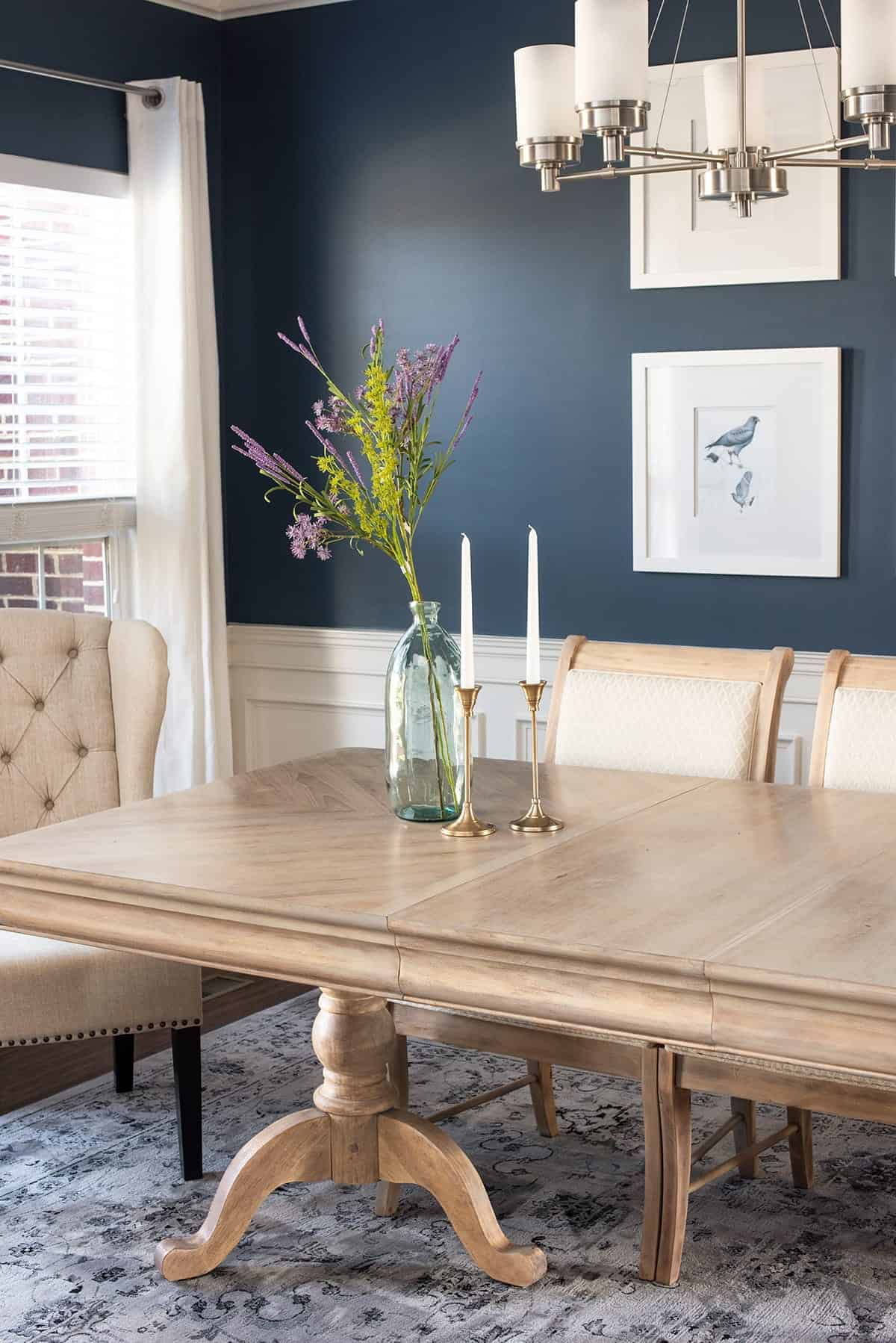Finished natural raw wood dining room table and dining room chairs. Cerulean blue walls with bird print, bud vase and brass candlesticks adorn table.