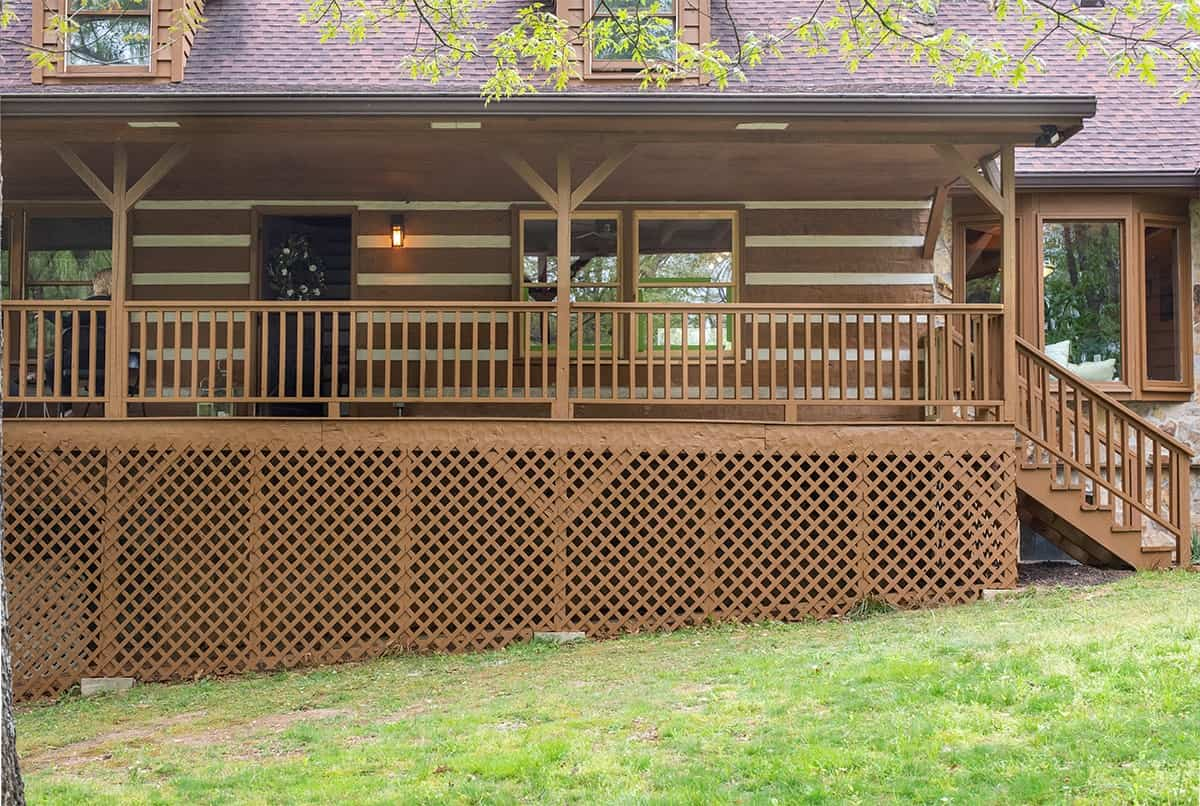 After photo of exterior of Rustic Modern Log home after exterior and lattice was stained with paint sprayer.
