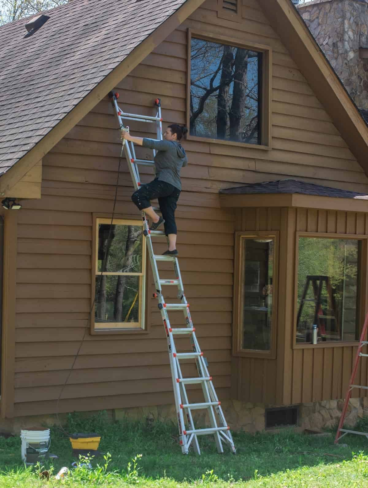 Side view of exterior of home midway through renovation. Woman on a ladder using paint sprayer to stain the home.