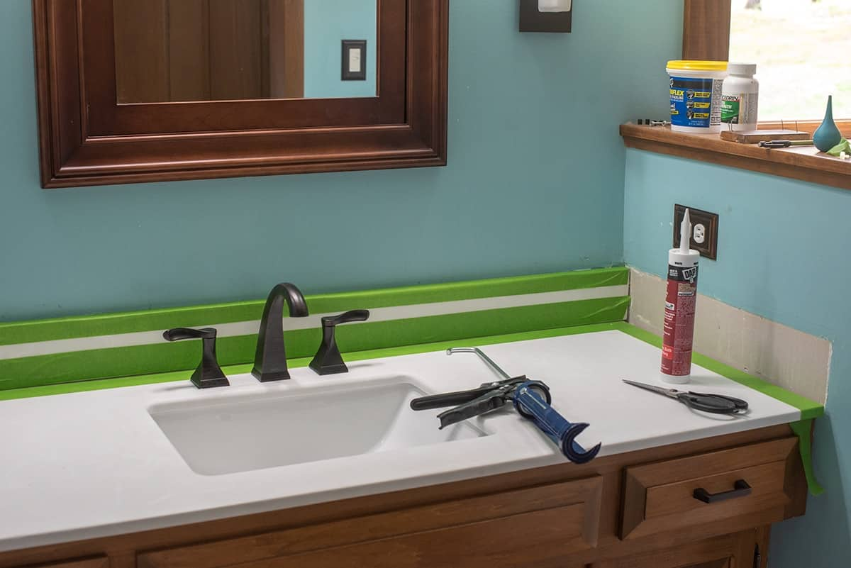 How To Caulk around a vanity. Image depicts new vanity top and tools required, taping technique.