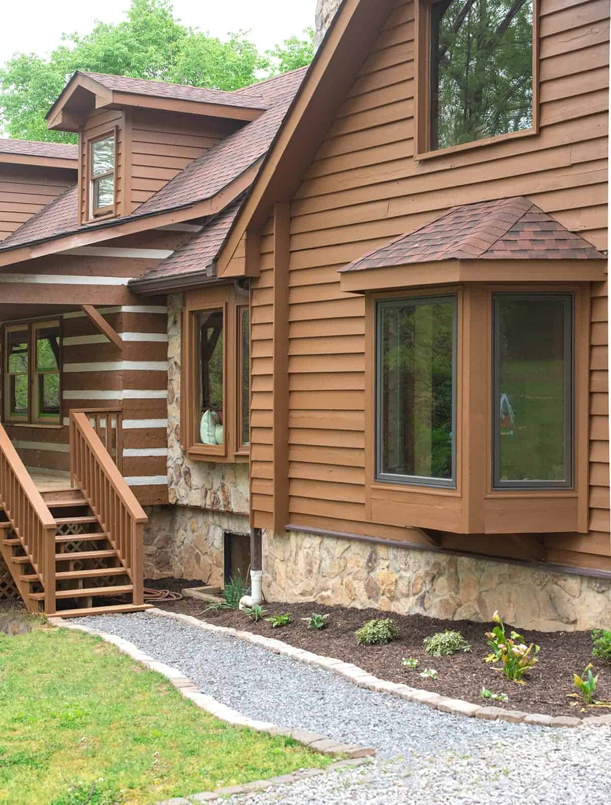 Gravel path with paver stone edging affordable walkway ideas. Log style cabin home with bay window overlooks new walkway and small garden.