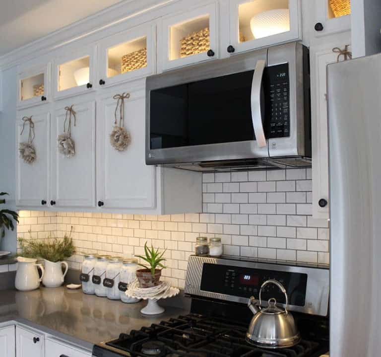 LED Cabinet Lighting against white subway tile back splash. Modern gray counter tops and white cabinets. White farmhouse style decor accents.