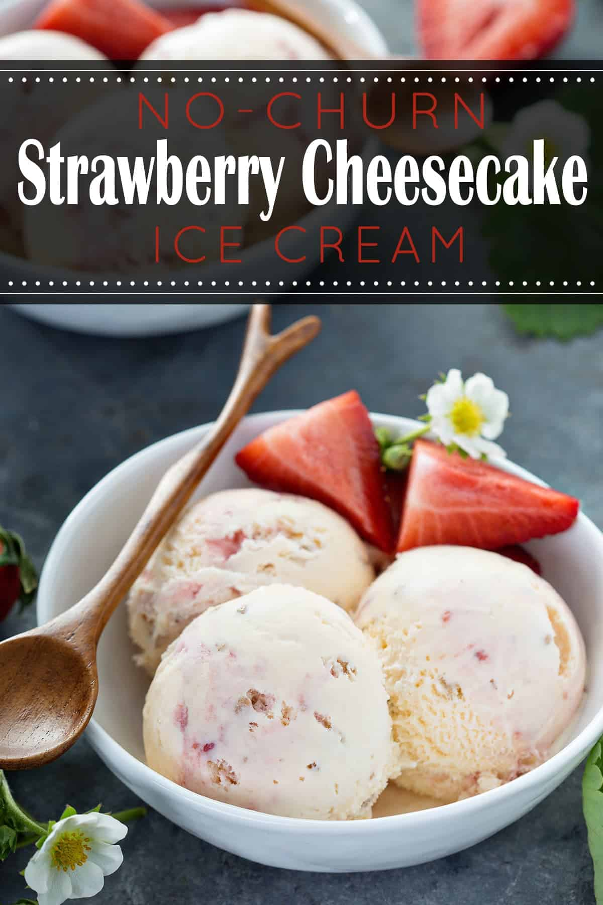 Scoops of decadent Strawberry Cheesecake ice cream in white bowl with sliced strawberries, daisy, and wooden spoon on black surface with recipe title.