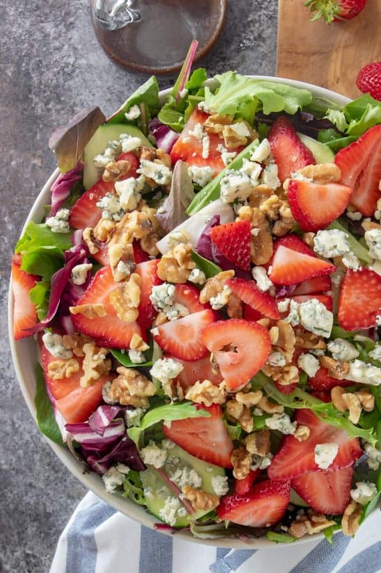 Strawberry spinach salad with feta crumbles and pecans in a salad bowl.