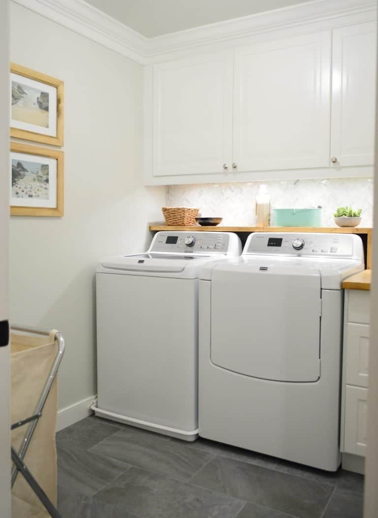 LED Wired Spotlight installed in laundry room under white cabinets. Wooden shelf installed above washer and dryer for storage and natural themed decor items.