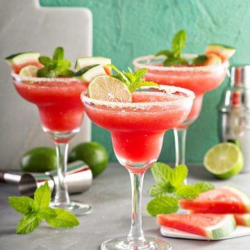Three frozen Watermelon Margaritas in glasses with sugar rim.