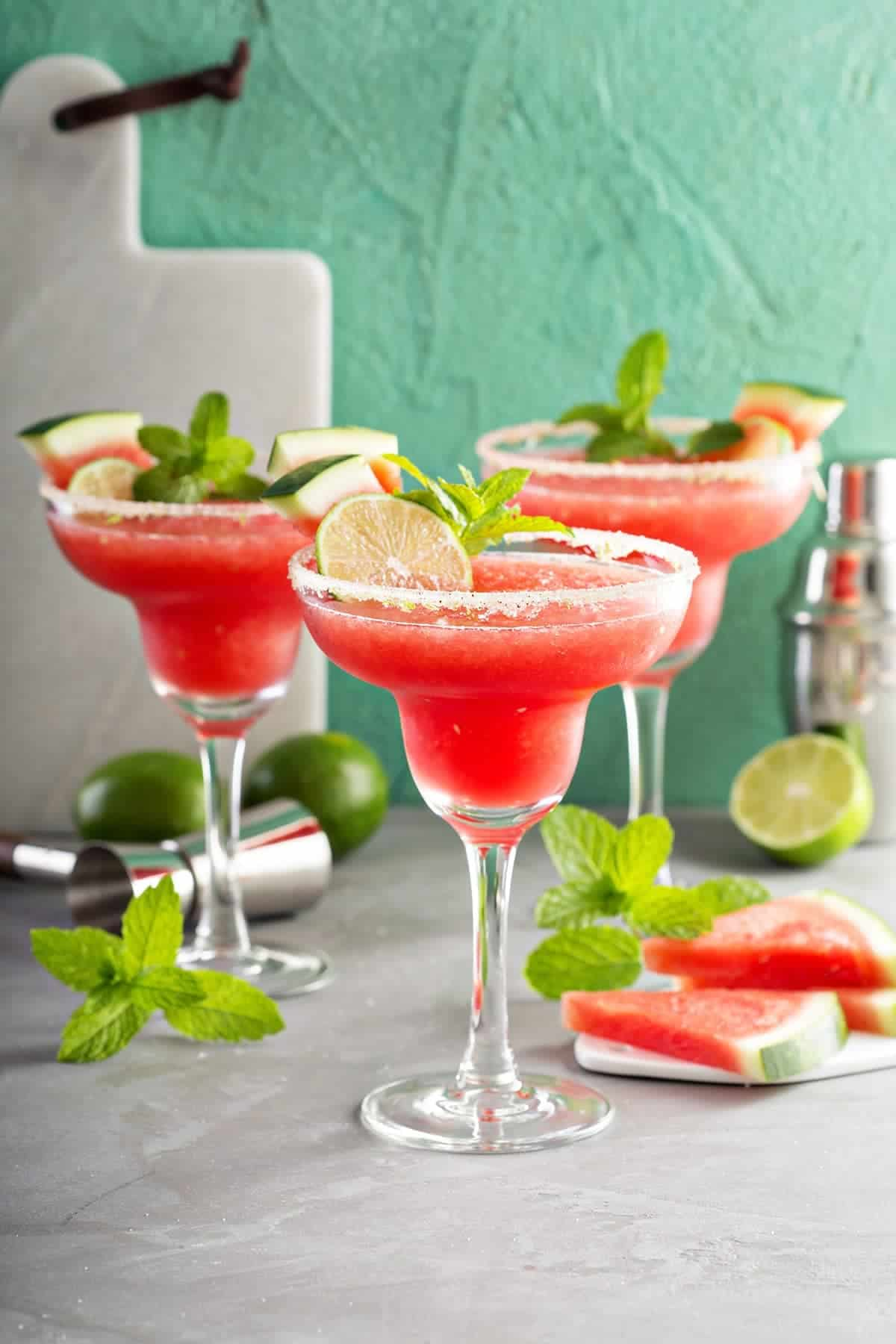 Watermelon margaritas with sugar rim and lime & mint garnish. Cocktail shaker, mint, limes and slices of watermelon in background for layering.