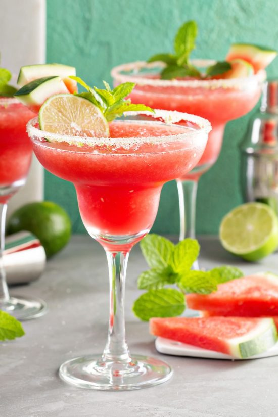Frozen Watermelon margaritas with sugar rim, mint, limes and slices of watermelon in background.