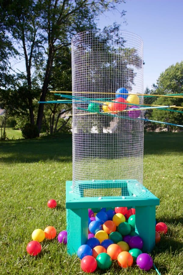 """Giant Kerplunk with colorful """"ballpit"""" style balls in a park-like grassy area."""