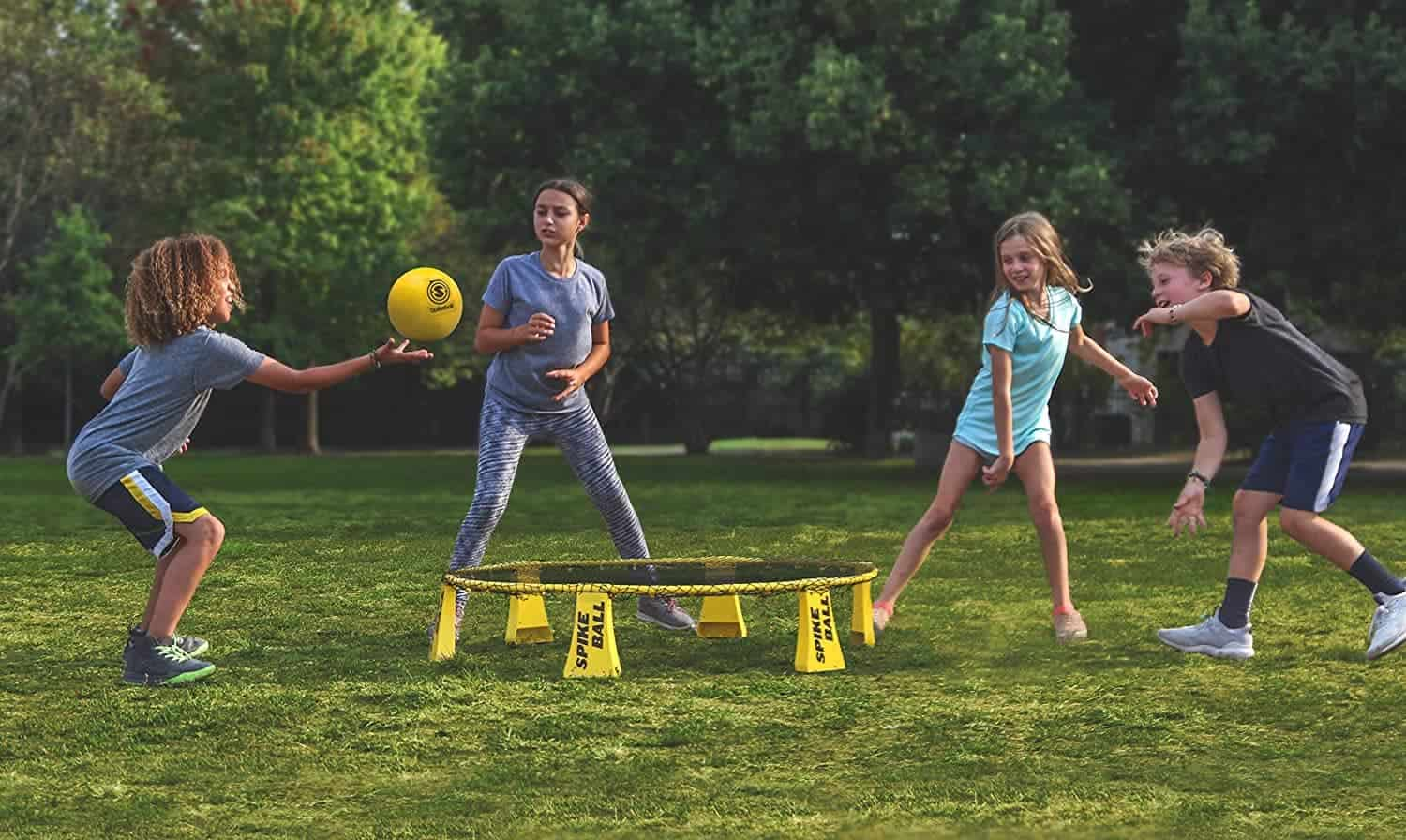 Spikeball outdoor game played by kids in a park-like setting.