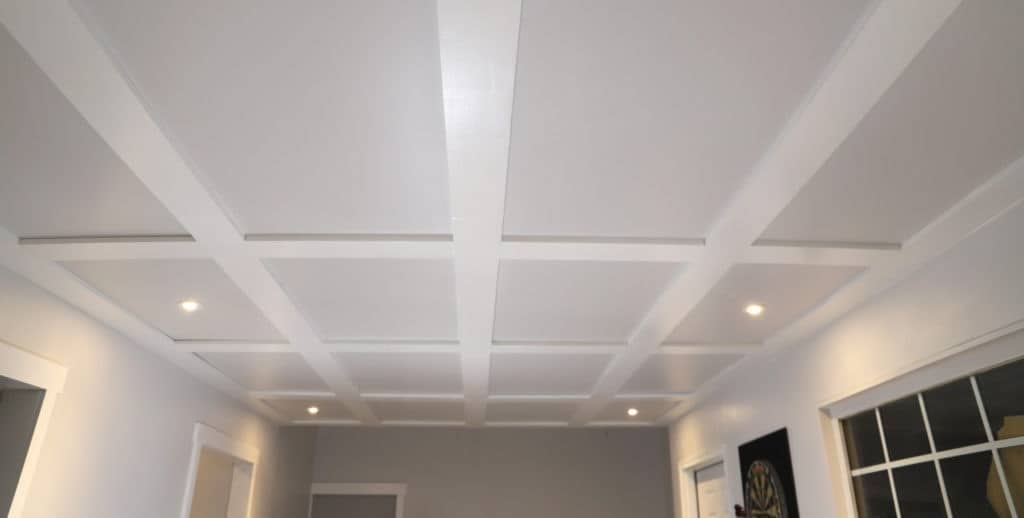 Gray and white coffered ceilings with hidden access in basement ceiling.