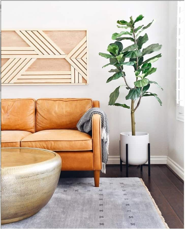 Modern living room with geometric wooden wall art piece above leather couch, potted plant, neutral area rug, and round metal coffee table.
