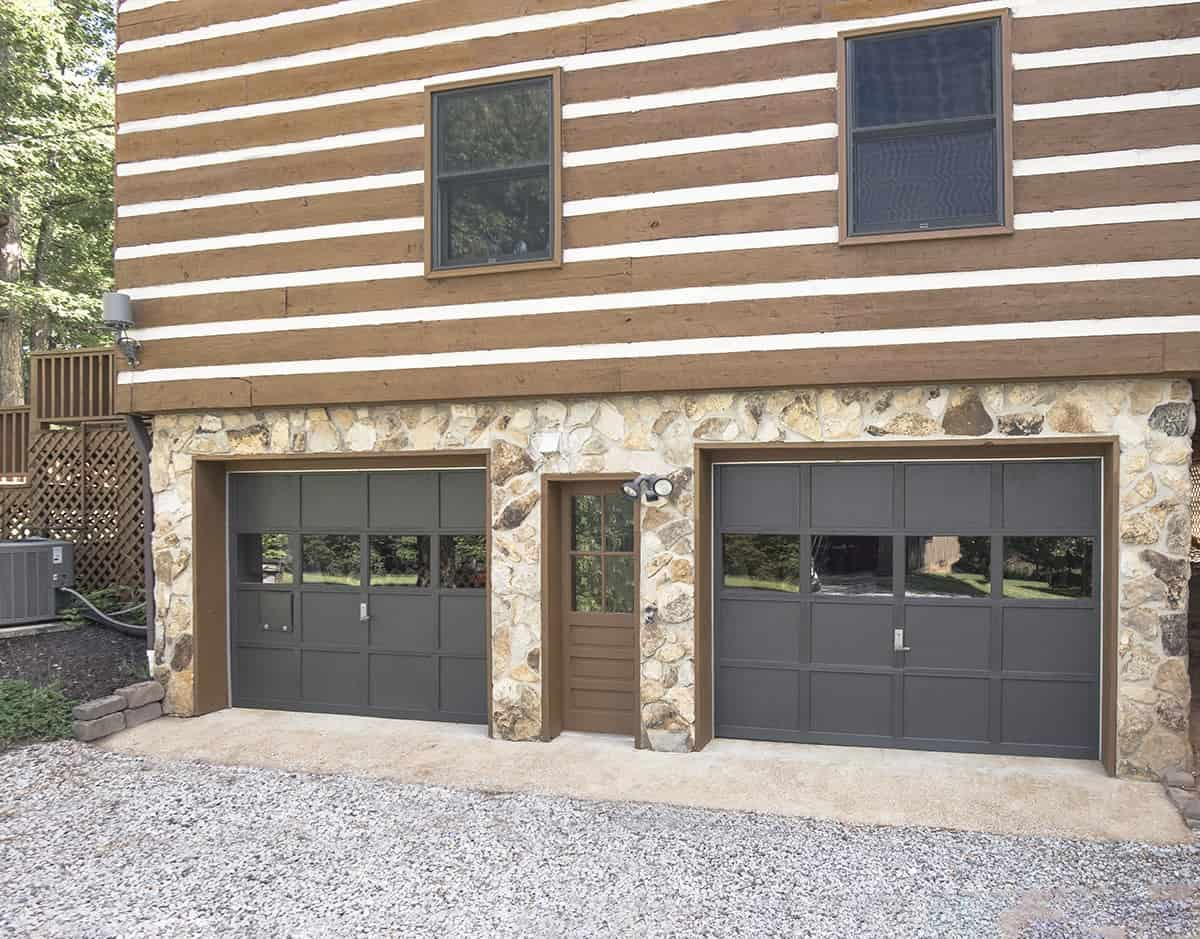 Garage doors painted black on a cabin style home.