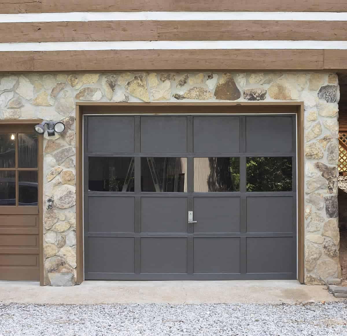 Black painted wooden garage door against stone exterior.