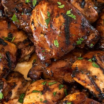 Closeup of grilled chicken thighs with grill marks on them.