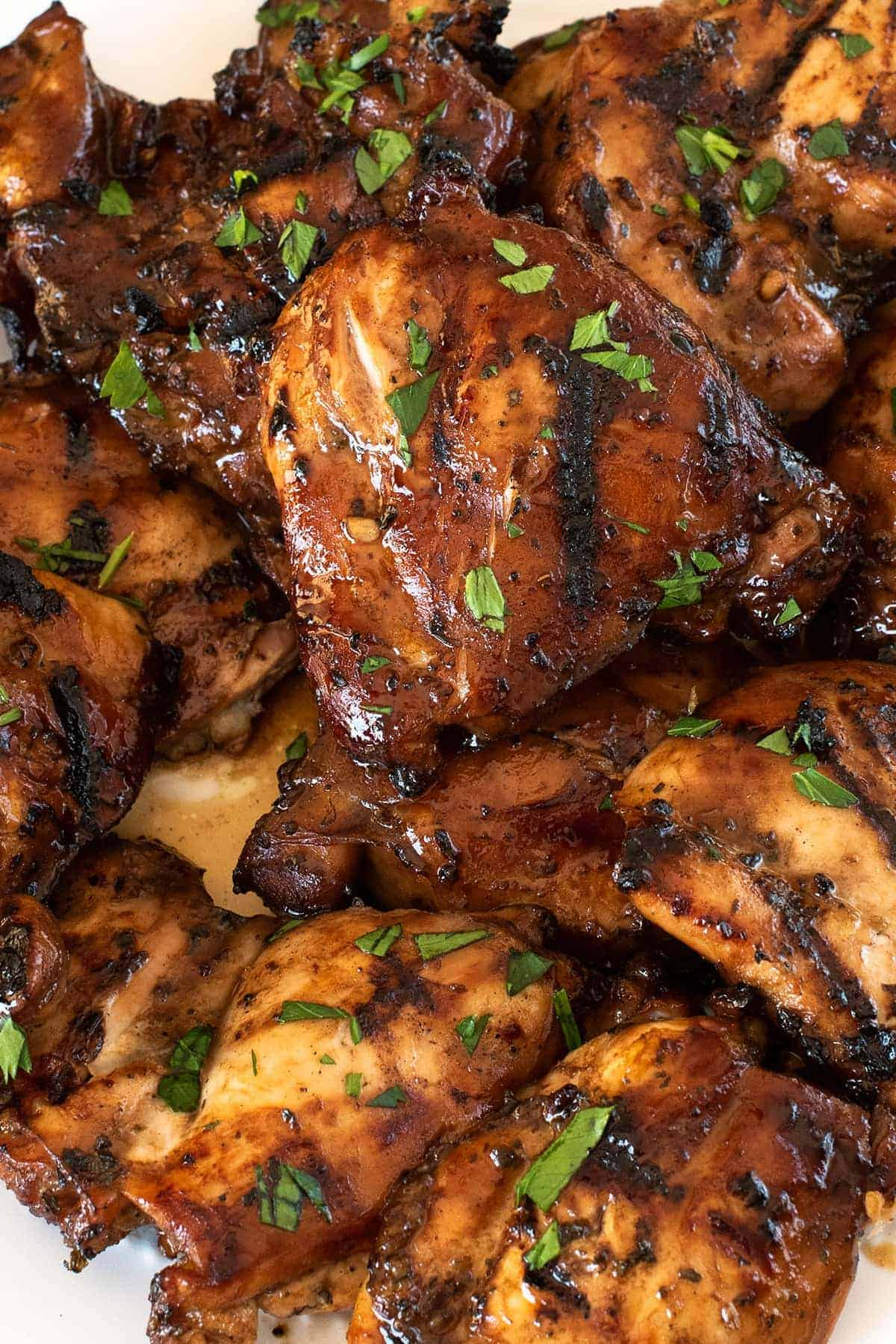 Freshly grilled chicken thighs with marinade and chopped fresh basil.