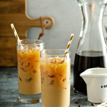 Glasses of Mixed Iced Latte Coffees with carafe and golden straws in the beverages.