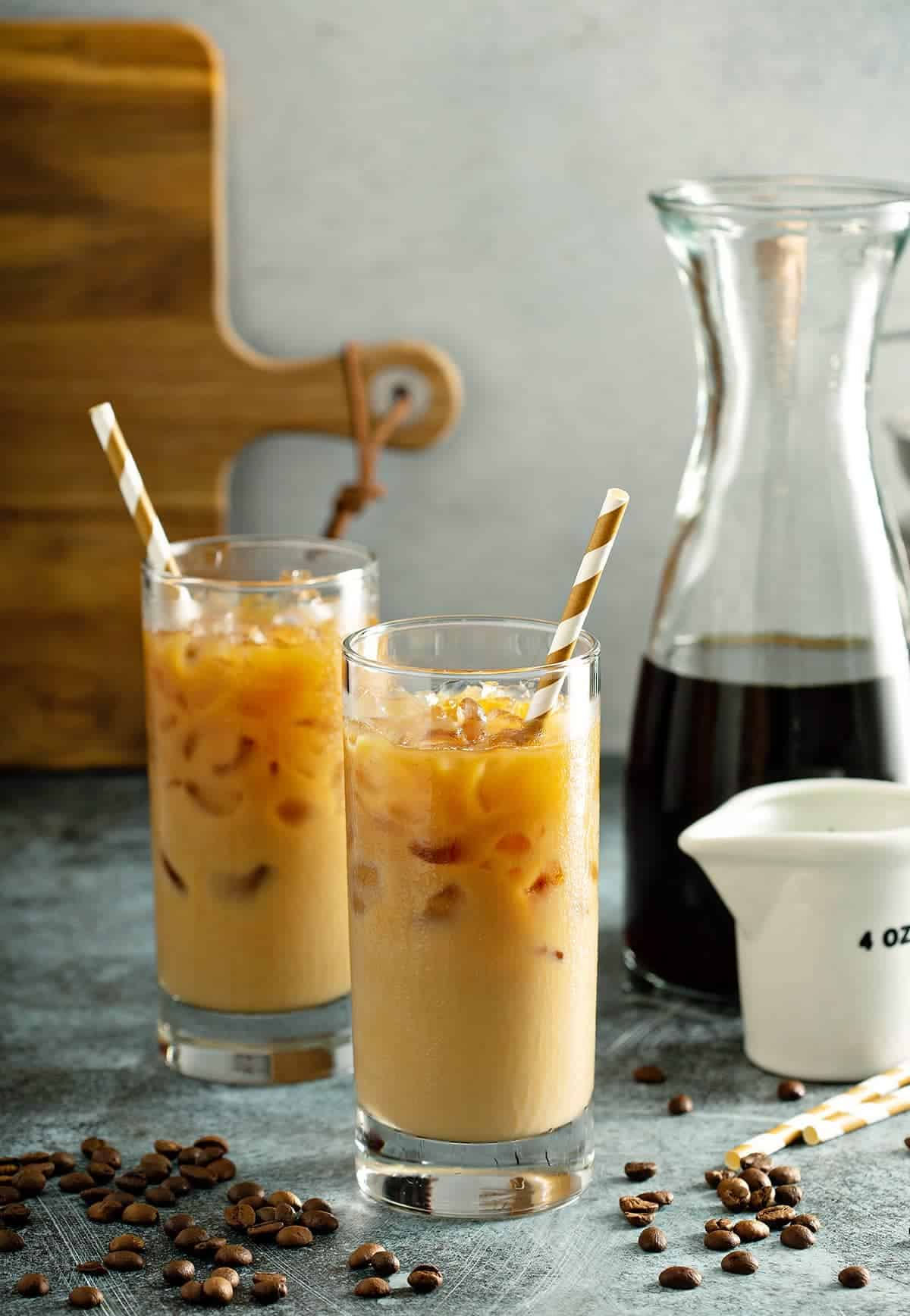Glasses of Mixed Iced Latte Coffees with carafe and golden straws in the beverages