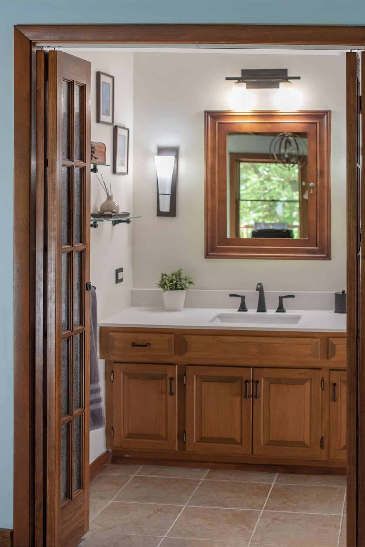 Updated modern farmhouse style bathroom with glass floating shelves and dark hardware. Wood framed mirror, door and wooden cabinets.