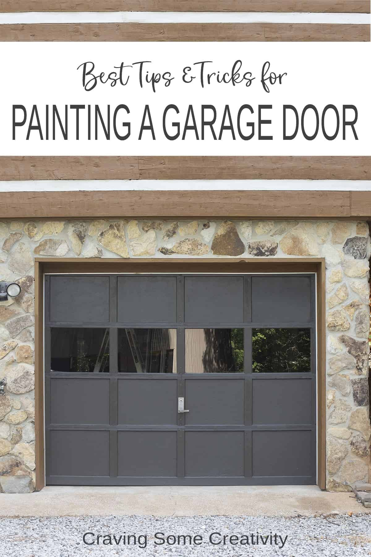 Front of painted grey garage door with stone facing around it.