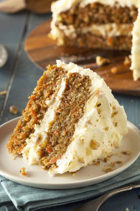 Slice of homemade carrot cake on a plate with walnuts sprinkled on top