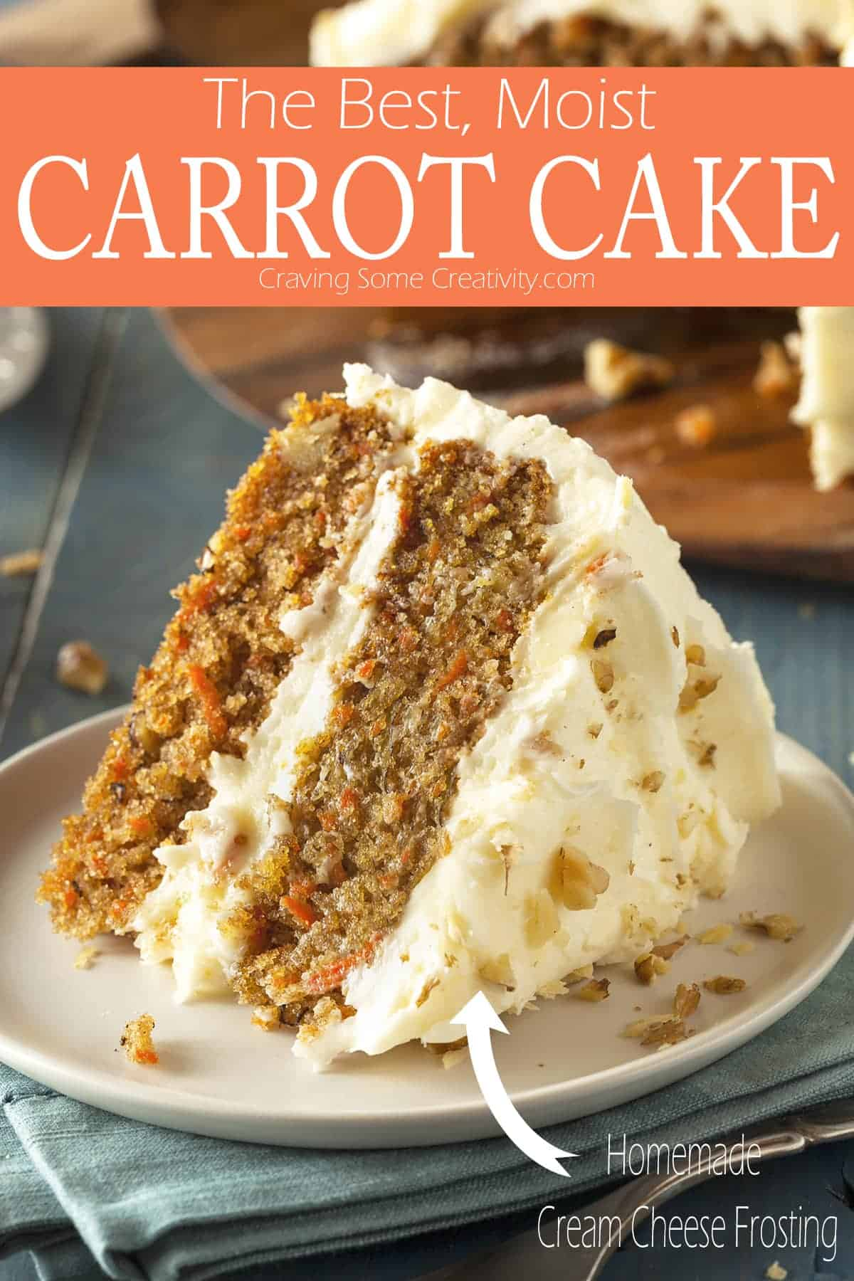 Double layered slice of cream cheese frosted carrot cake on white plate over folded blue towel next to full cake on wooden tray.