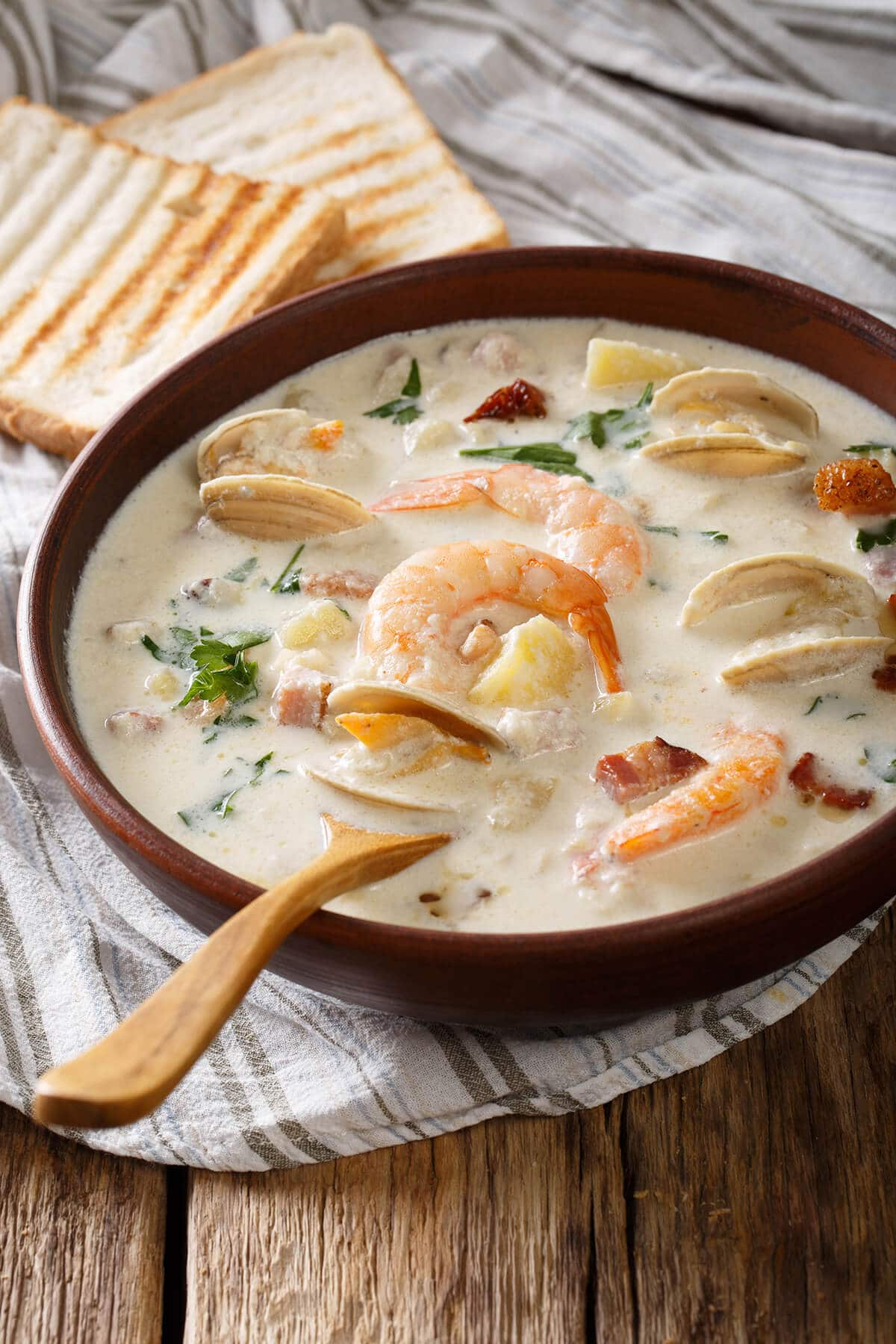 Creamy Seafood Chowder soup with shrimp & mussels. Wooden spoon and toasty bread on the side