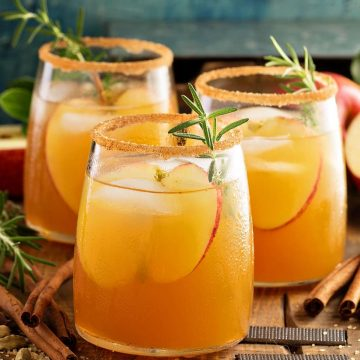 Side view of three glasses of caramel apple sangria on a rustic wood board. Cinnamon sticks lay around the glasses with slices of apple and herbs as garnish.