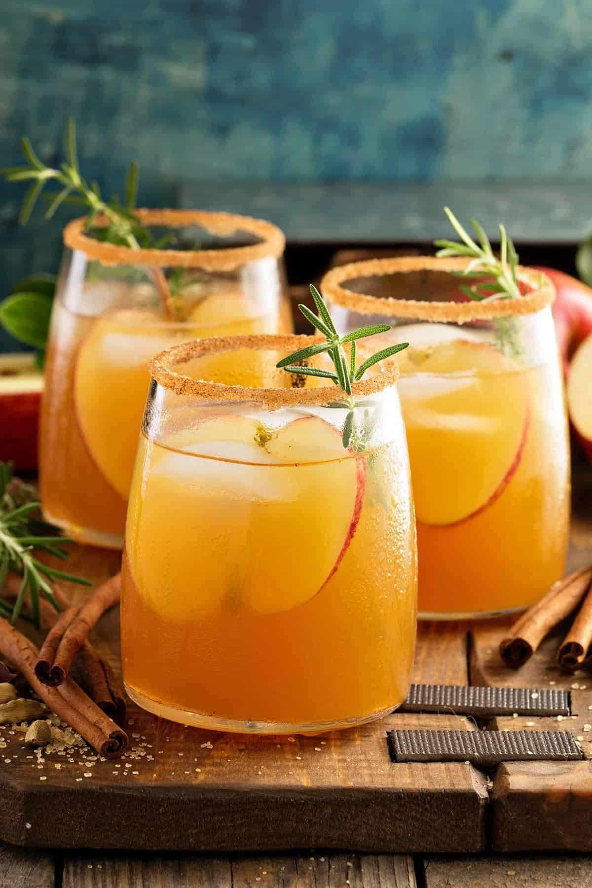 Several glasses of Caramel Apple Sangria with apple slices and rosemary garnish