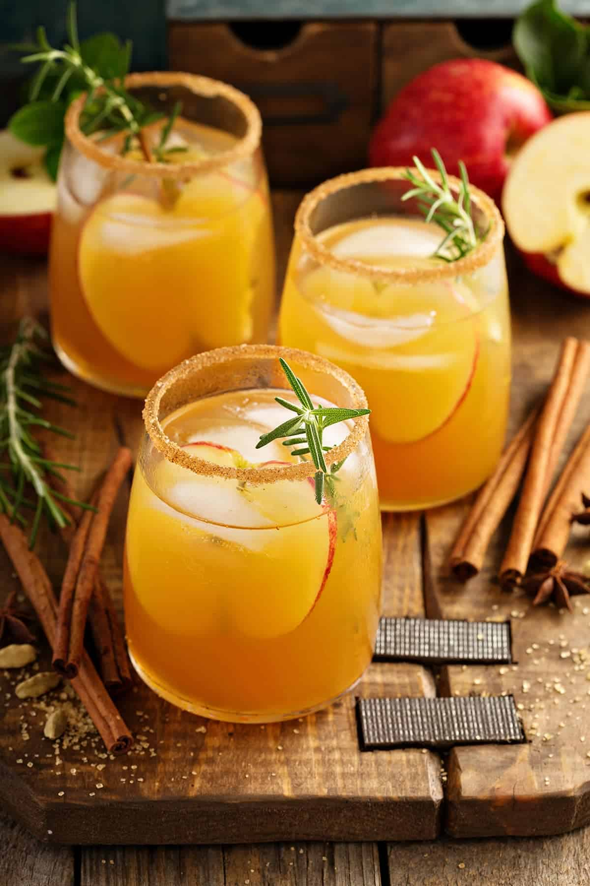 Fall Caramel Apple Cider Sangria with cinnamon sticks and rosemary on a rustic board