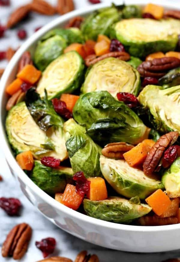 Maple roasted brussel sprouts with chopped squash, cranberries, and pecans in white bowl.