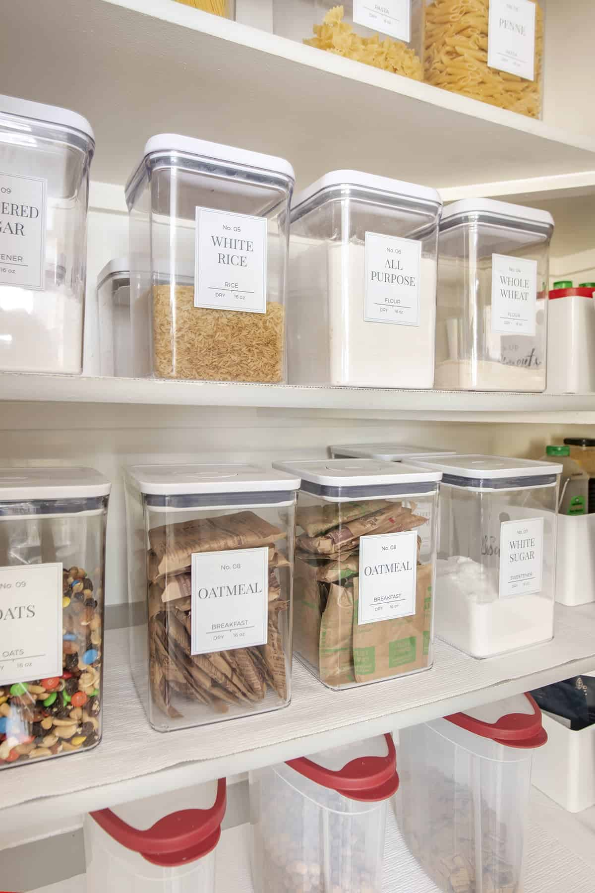 Clear labeled canisters keep staples like rice, flour and oatmeal orderly on pantry shelves. Clear plastic pour bins keep cereal fresh on the bottom shelf.
