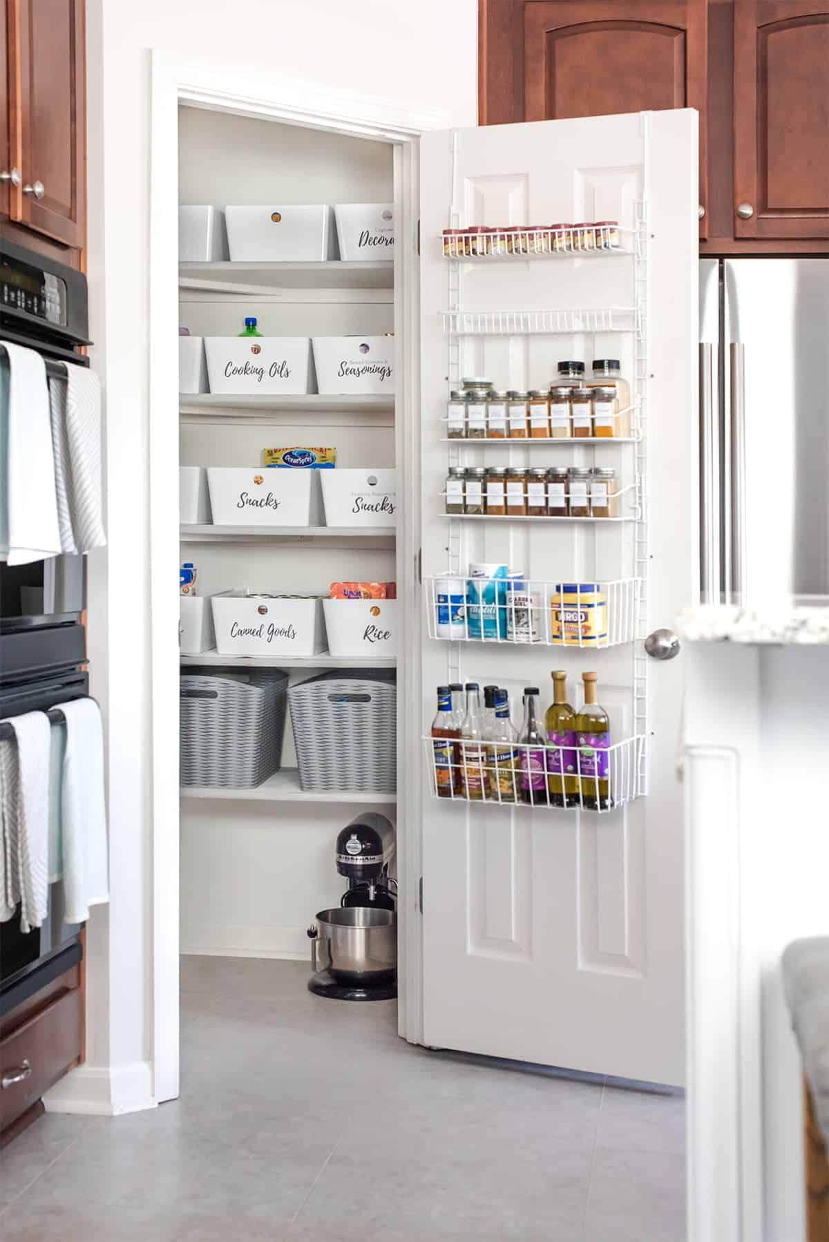 Full size shot of organized pantry. Over-the-door storage rack for spices. Labeled uniform bins on shelves.