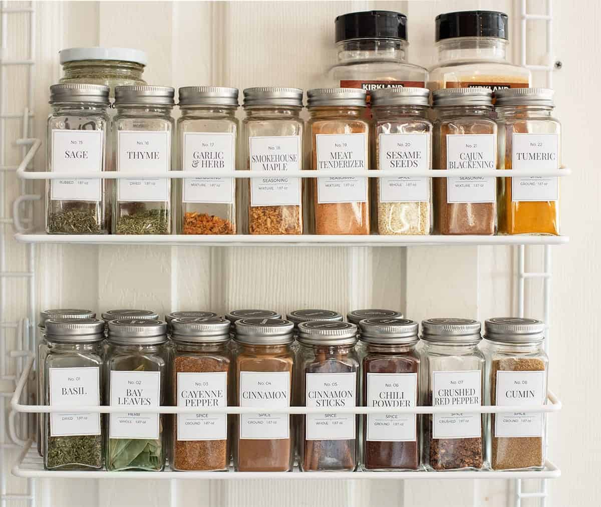 Spice rack organizer arranged with clear glass spice jars labeled with contents.