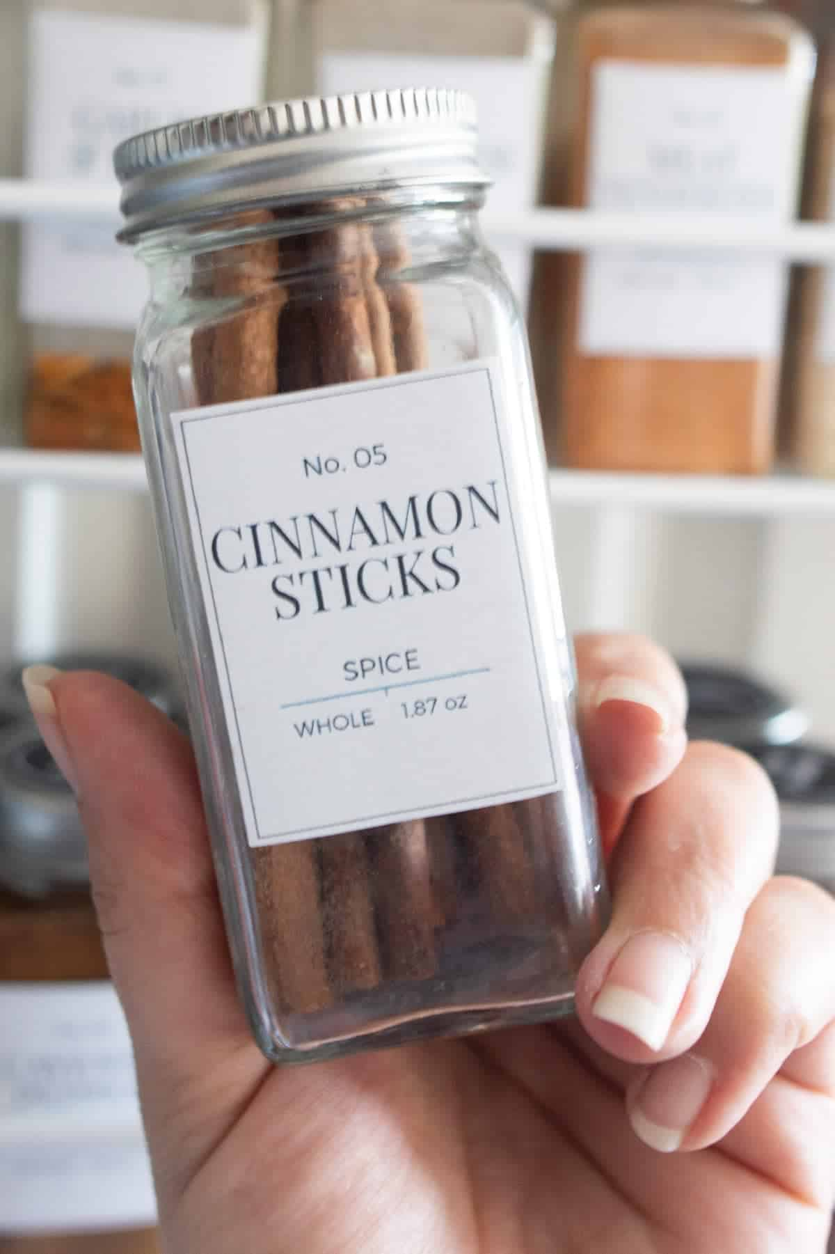 Cinnamon sticks label on clear glass spice jar filled with cinnamon sticks.