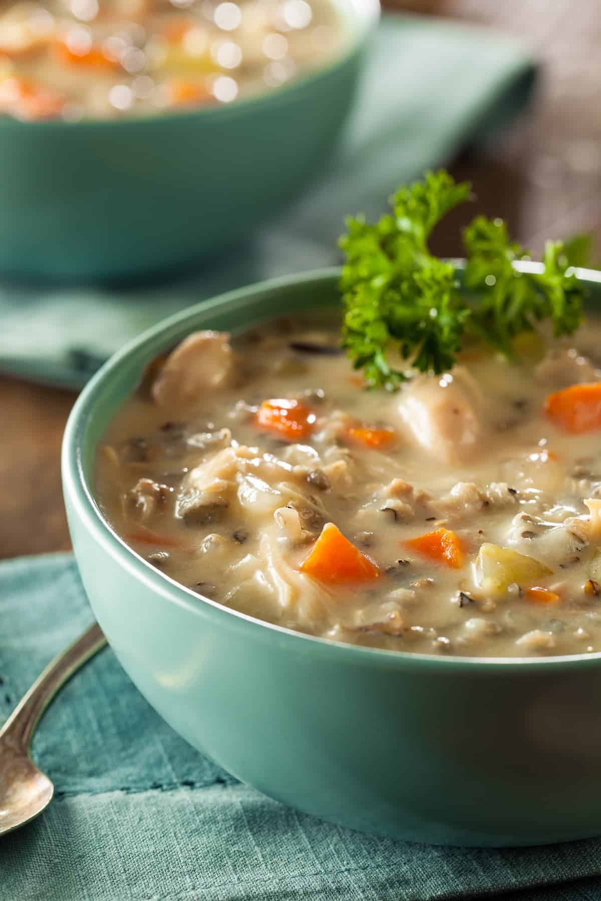Texture Closeup of Creamy Chicken and wild rice soup with aqua soup bowl and spoon on wood board background.