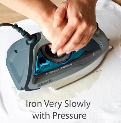 Hands pressing on iron to transfer an image using photo transfer paper.