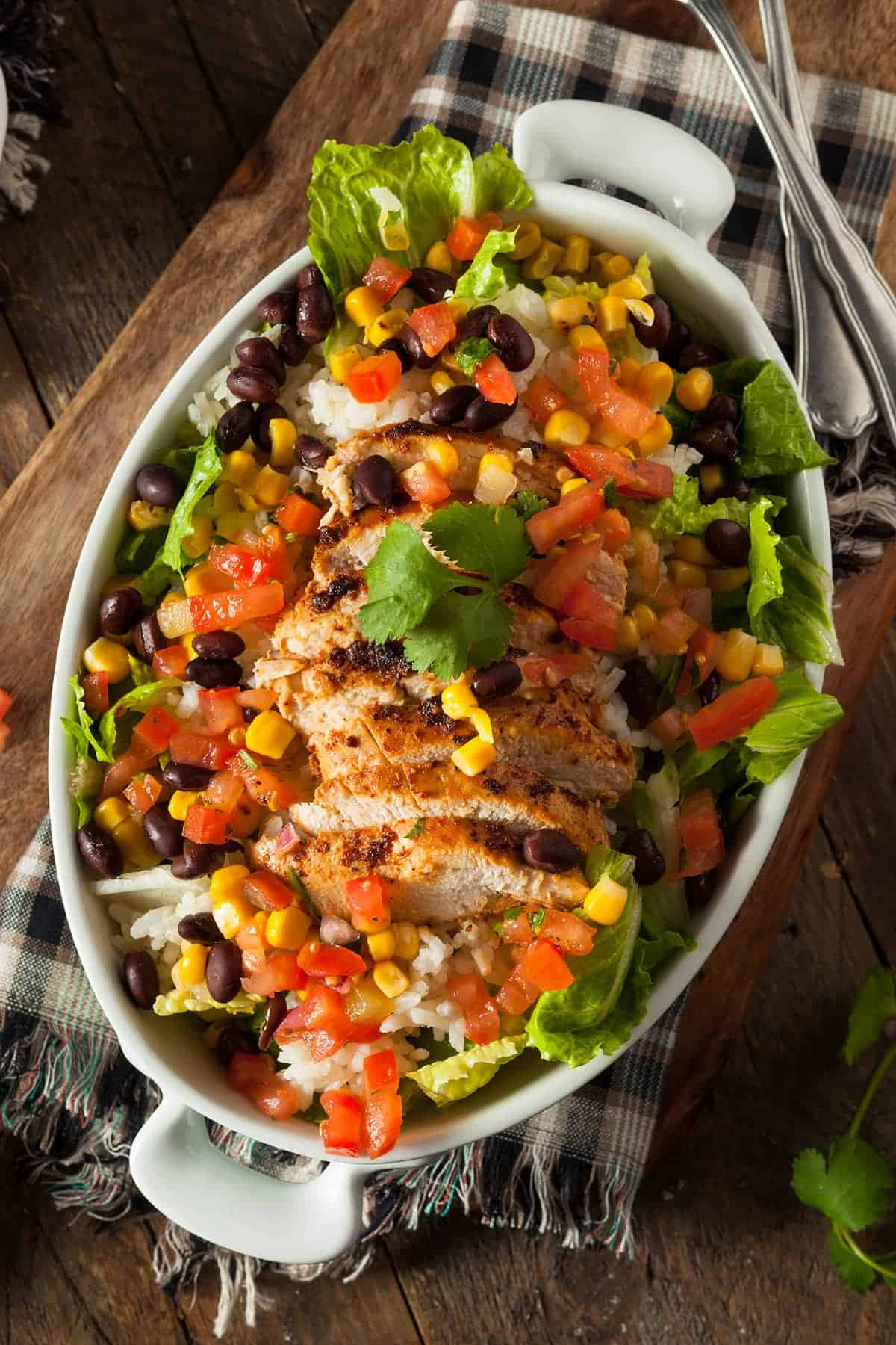 Chicken burrito topping ideas including tomatoes, corn, black beans, lettuce, rice, and sauce.