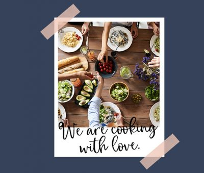 Polaroid of people gathered around a table set with food and passing the food around. Text Overlay reads we are cooking with love.