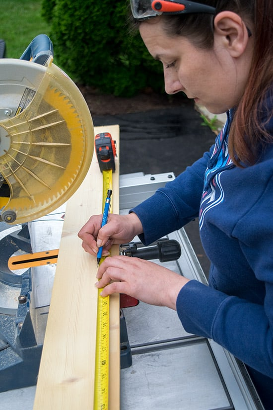 The owner and writer of Craving Some Creativity, Rachel, measuring wood on a table saw.