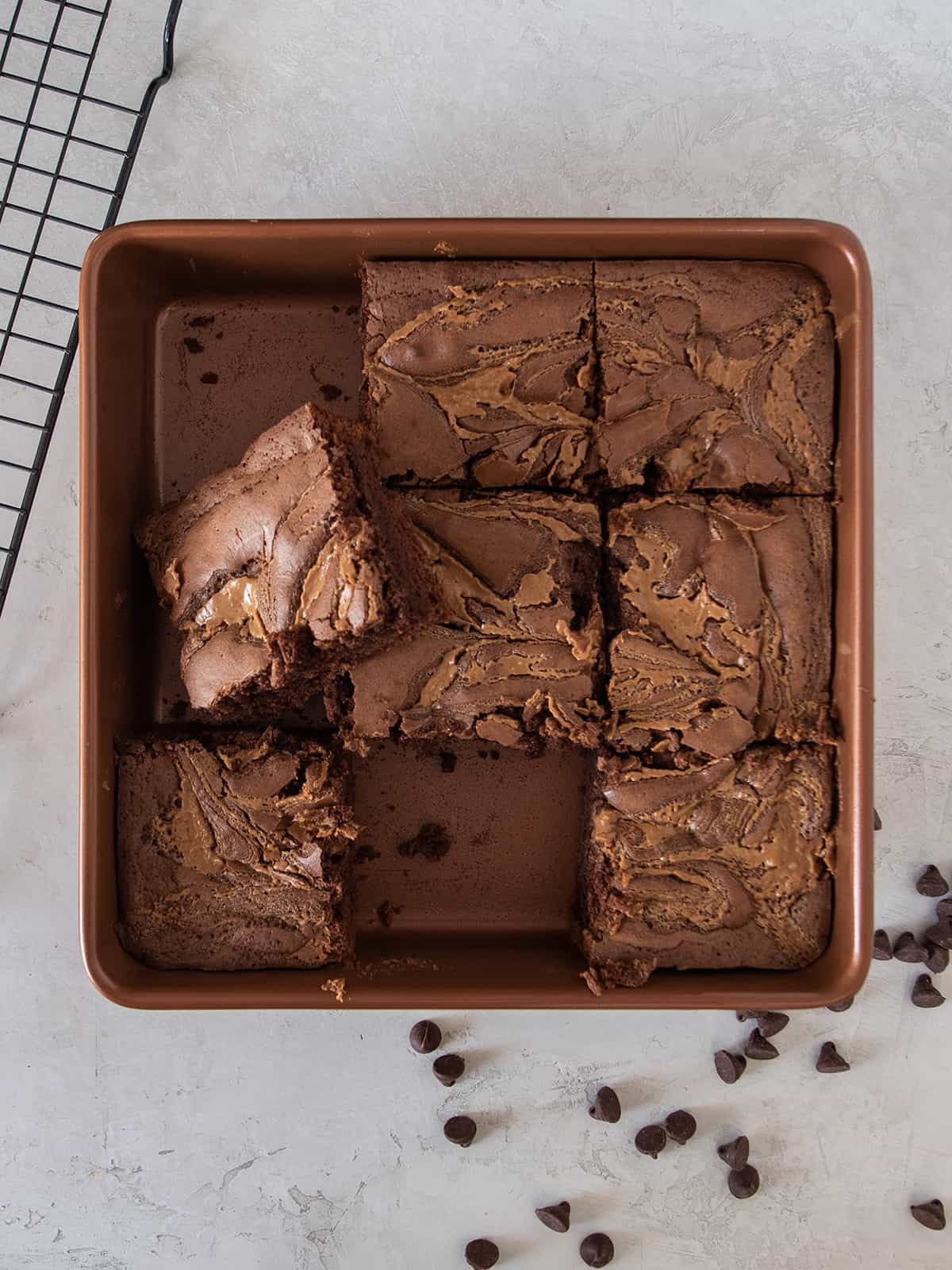 A tray of marbled peanut butter brownies with a brownie removed and another stacked on top.