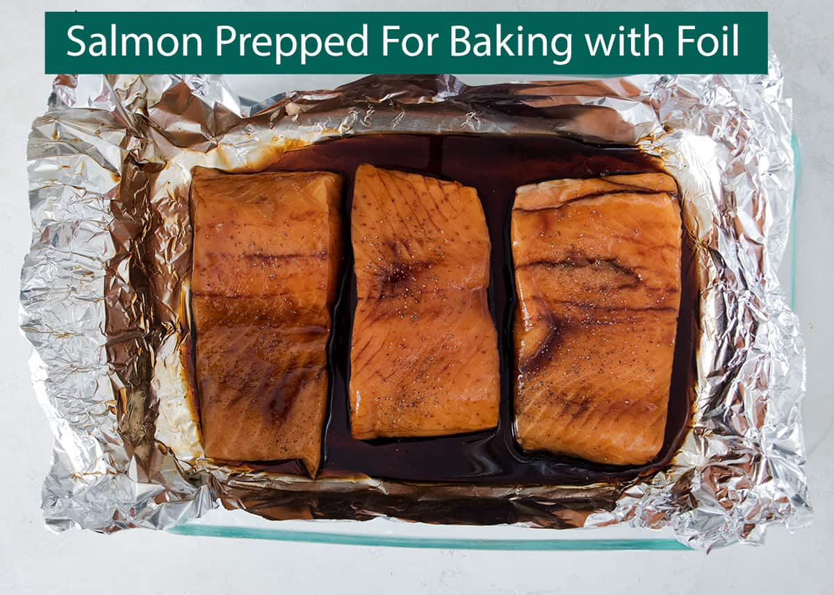 Salmon filets in foil lined pan ready for baking with teriyaki sauce poured over.