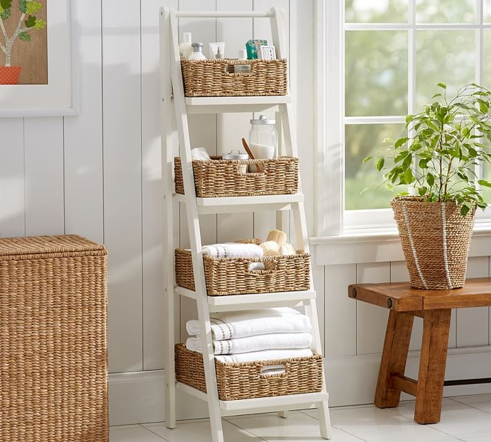 White ladder shelves filled with baskets and toiletries while leaning again white wall.