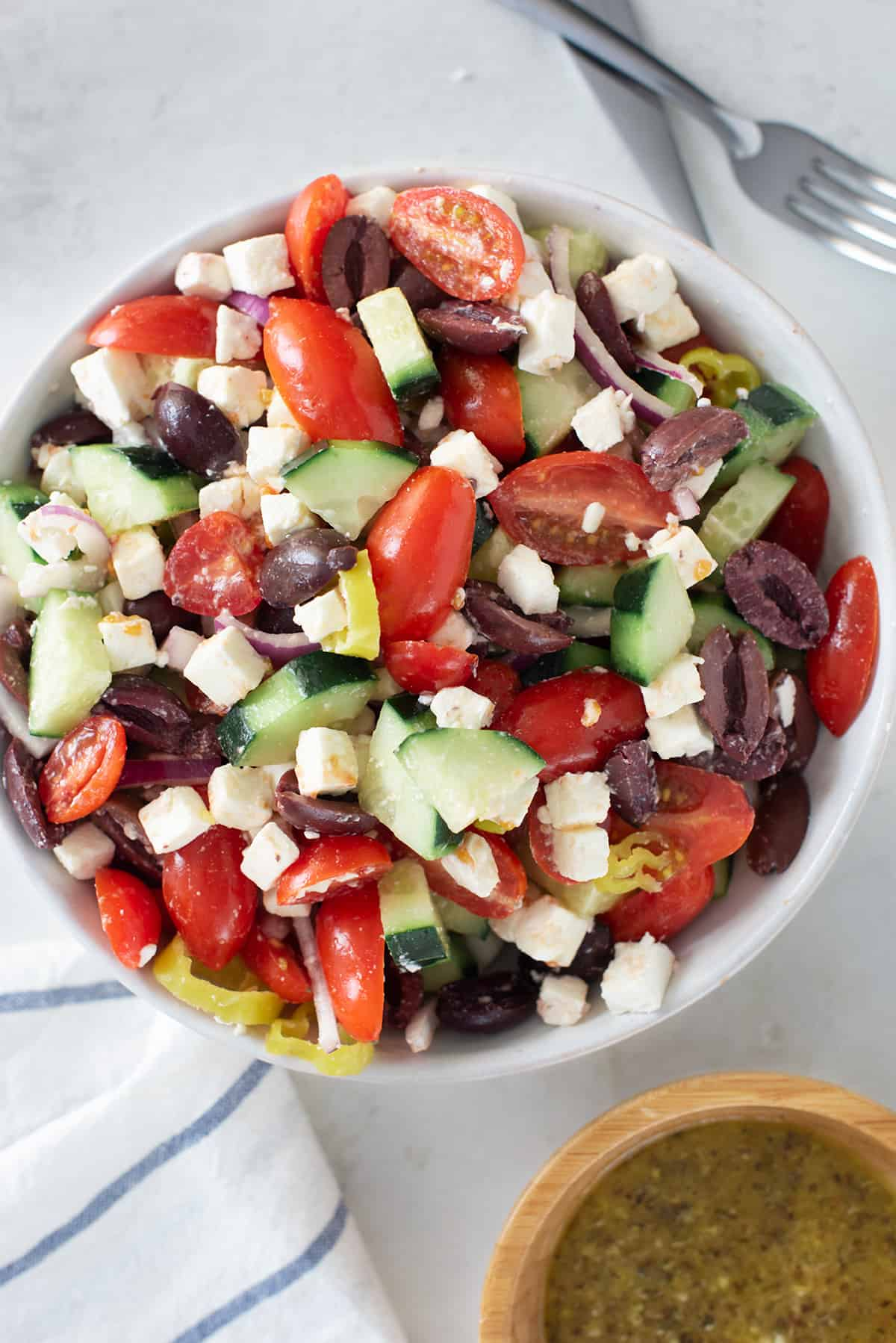 Greek salad filled with lettuce, kalamata olives, tomatoes, red onion, cucumbers, feta cheese, and croutons in large white bowl next to glass bottle of vinaigrette.
