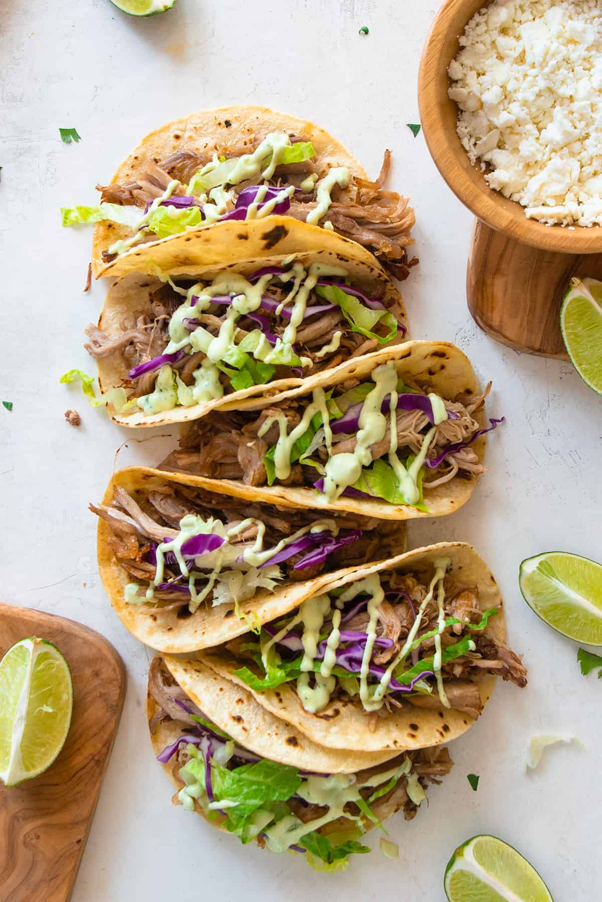 Carnitas Tacos laid out in a row and open.
