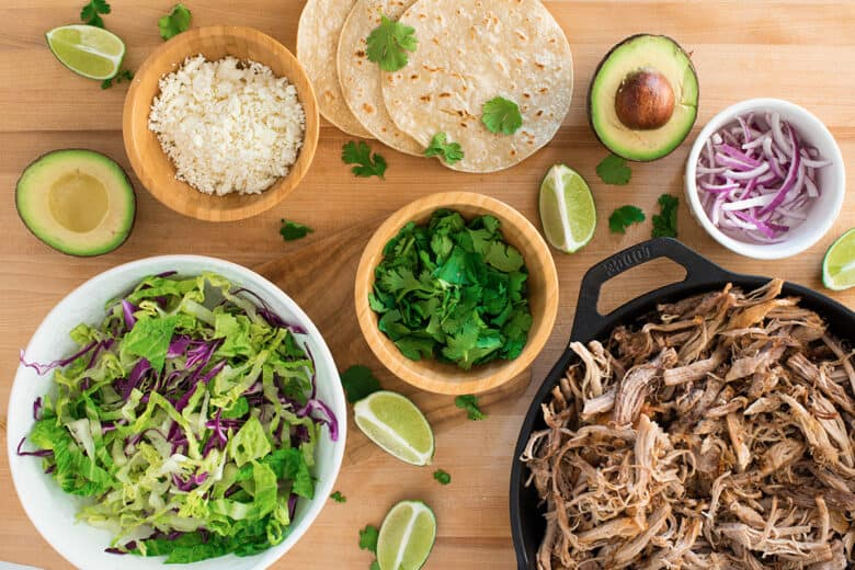 Flat lay of taco topping ideas like red onions, lime wedges, cheese, and cilantro.