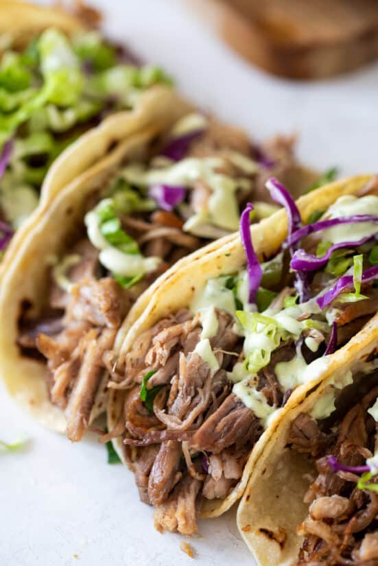 Carnitas tacos lined up in a row with slaw and sauce on top.