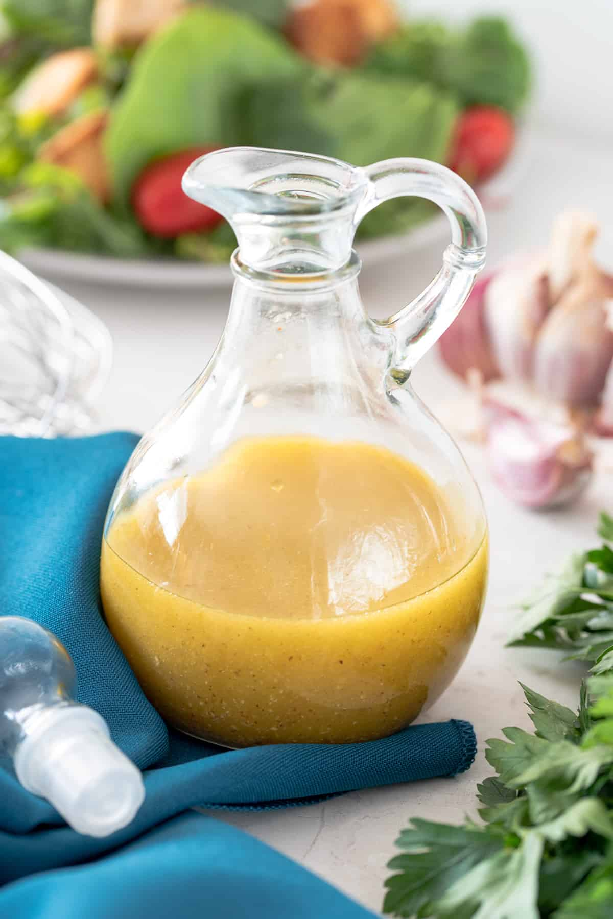Cruet Bottle of White Balsamic Salad Dressing with ingredients scattered around.
