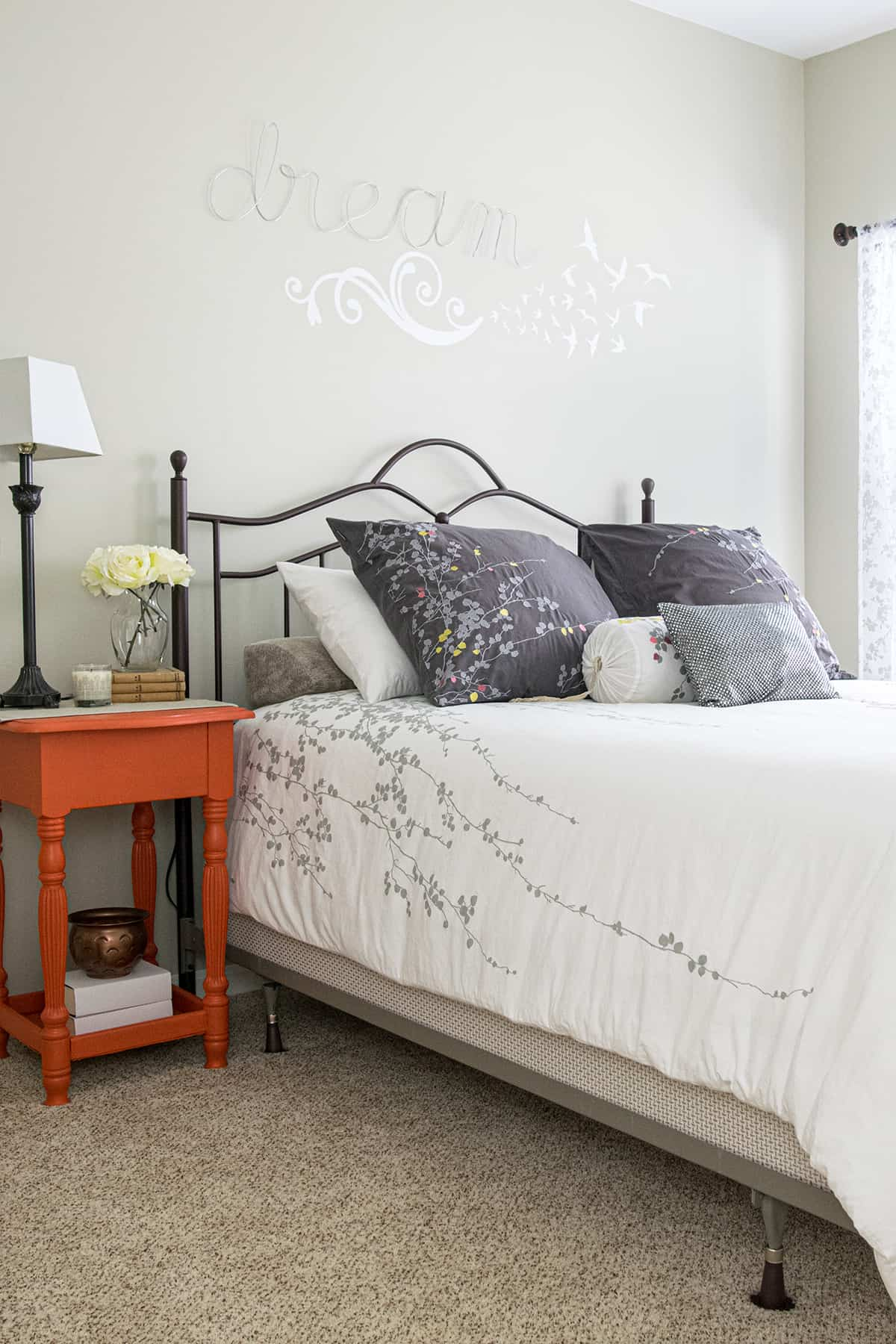 Neutral bedroom with white floral comforter, orange side table, and art over the bed.